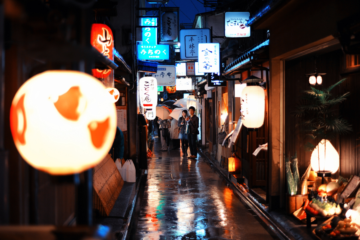 Narrow streets of historical part of Kyoto decorated with all kinds of traditional japanese lanterns at a rainy city night. Island of Honshu, Japan